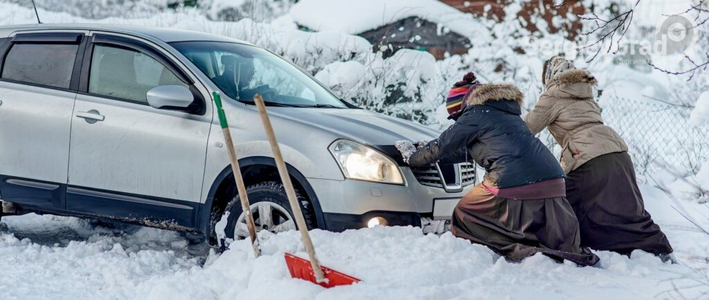 Выталкивают машину из сугроба